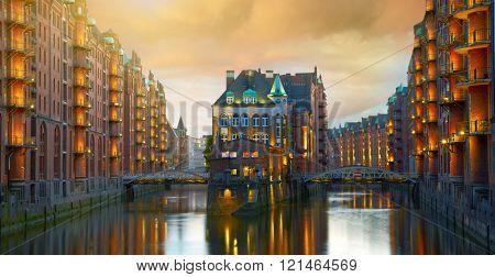 Old Speicherstadt in Hamburg illuminated at night. Sunset background