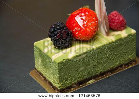 A Green tea cheese cake ontop raspberrybluberrystrawberry ** Note: Shallow depth of field