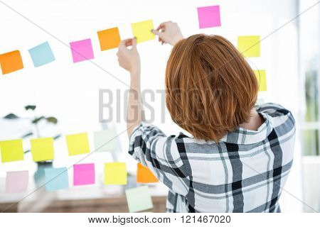 hipster woman facing away from the camera, sticking up coloured paper suares
