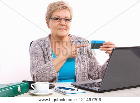 Elderly senior woman showing credit card, paying over internet for utility bills or shopping