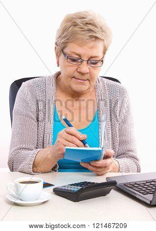 Elderly Senior Woman Writing In Notebook Or Calendar