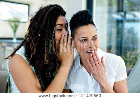 Lesbian couple whispering in ears and looking surprised poster