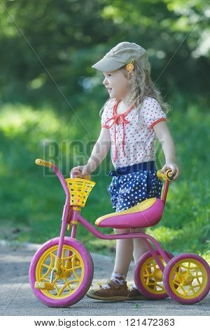 Two year-old standing near pink and yellow kids tricycle with steel frame