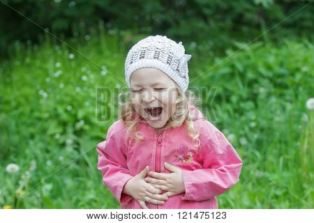 Little Caucasian girl bending with belly laughter in spring green garden