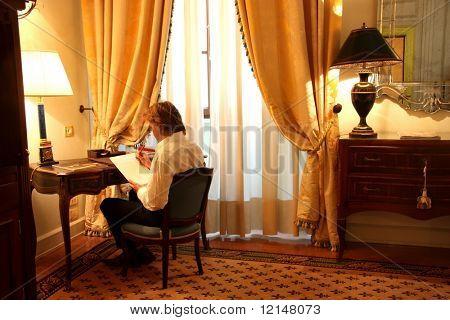 a man  write in  a luxury hotel room