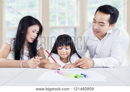 Beautiful little girl doing schoolwork with parents