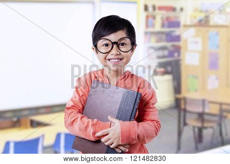 Beautiful little student holds book in class