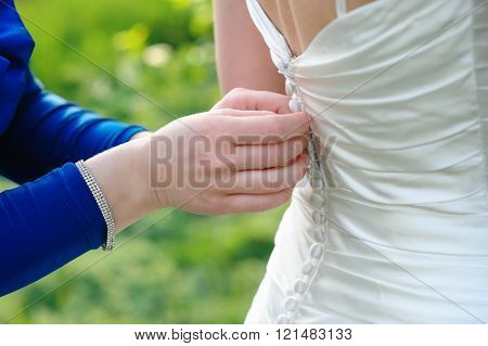 Bridesmaid is helping the bride to dress in weddihg day