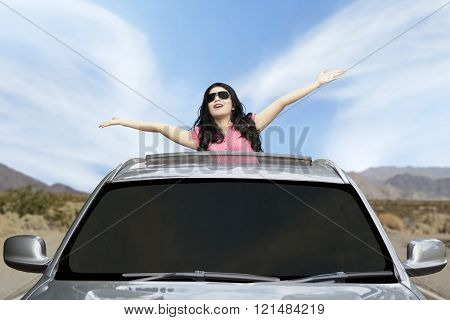 Happy woman raised hands on the sunroof