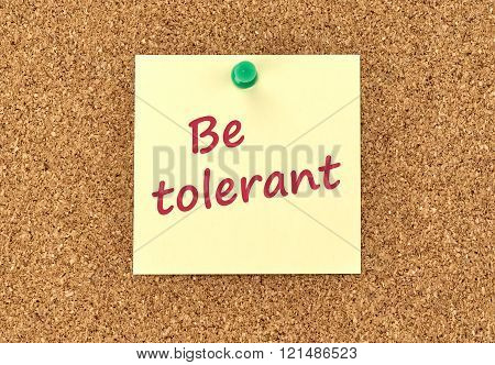 The phrase Be Tolerant in red text on a yellow sticky note posted to a cork notice board. poster