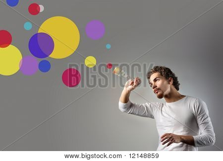 young man painting circle on a grey background
