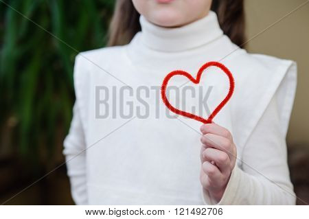 Red Wire In The Form Of Heart In The Hands Of A Girl