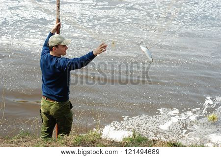 The Man Caught A Fish. He Pulls His Hand To Get It From The Network