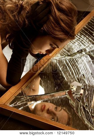 image of a beautiful woman in a  broken mirror