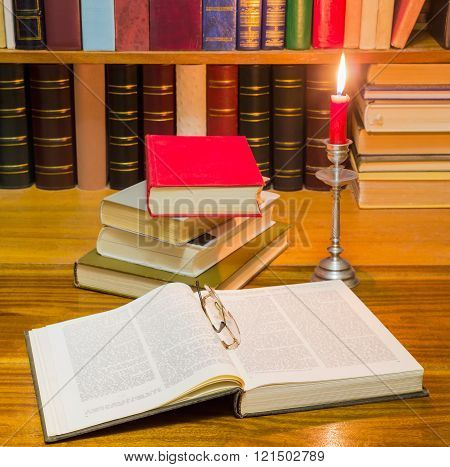 Open book and other books on a table by candlelight