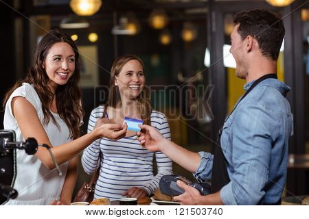 Smiling clients paying with card at the bar