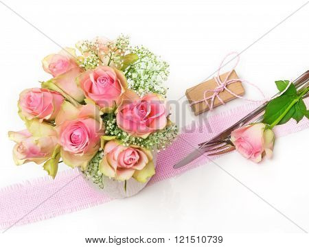 pink roses with geschent and cutlery on a white background