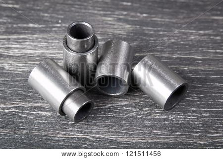 Metal cylinders - elements of the industrial roller driving chain on dark background