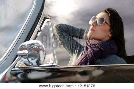 portrait of beautiful woman sitting in a vintage car