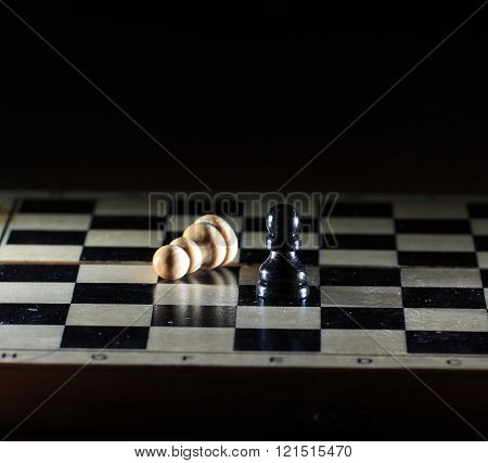 Composition with chessmen on glossy chessboard  on a black background