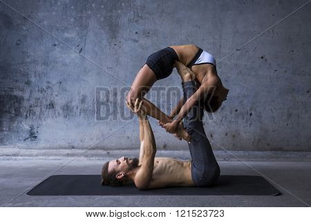 Acroyoga practice, man on woman on a urban background