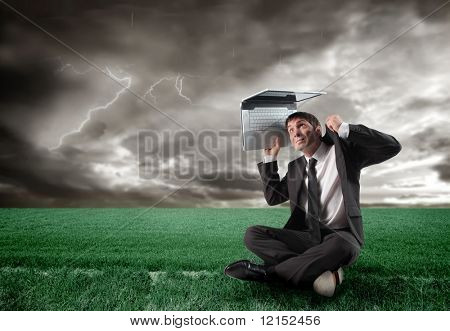 businessman with laptop under a storm