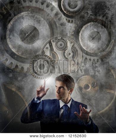 business man moving gear of big mechanism