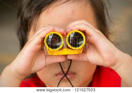 Little Asian Girl Looking Trough A Binoculars