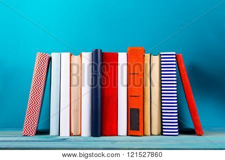 Stack of colorful books, grungy blue background, free copy space