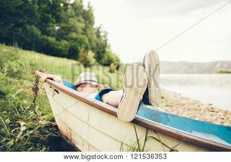 Boy lying in old boat near the lake