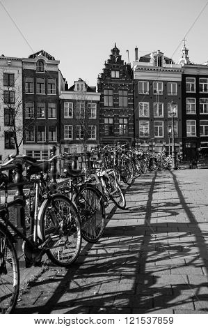 AMSTERDAM NETHERLANDS - 16TH FEBRUARY 2016: Lots of bikes chained to the railings of a bridge in Amsterdam. Typical Amsterdam style buildings can be seen in the background.