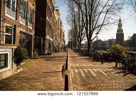 AMSTERDAM NETHERLANDS - 17TH FEBRUARY 2016: The outside of a building in Amsterdam in the morning. Bikes cars and the Montelbaanstoren Tower can be seen.