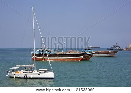 GULF OF ADEN, DJIBOUTI â?? FEBRUARY 08, 2016: Luxury sailing boat, fishing and cargo ships at anchor in the port of Djibouti