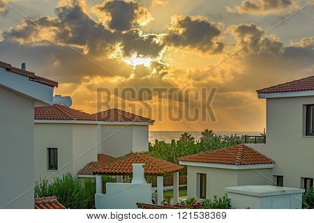 Sunset over luxurious holiday beach villas for on Cyprus