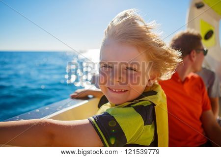 little kid boy enjoying sailing boat trip