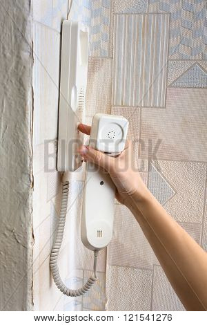 Hand Pressing A Button On The Intercom At Home