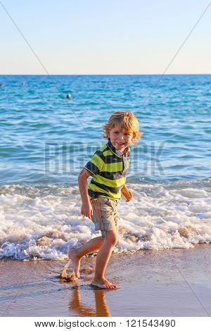Happy little kid boy having fun with running through water in oc