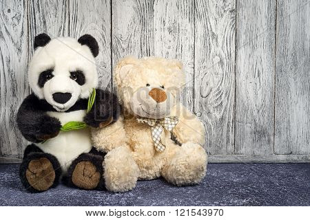 Teddy Bear And Panda Beer Toys Sitting On Floor On Wooden Background Copy Space For Text. Toy Birthd