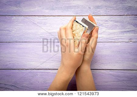 A Female Hands Hold A Small Box With Present On The Wooden Desk Top View With Copy Space