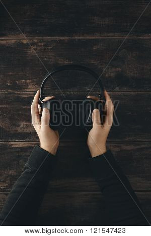 Top View Two Hands Hold Wireless Headphones With Leather Earpads