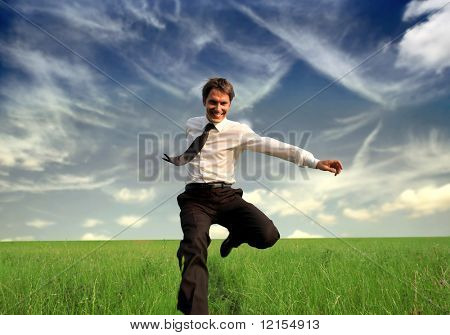 happy business man jumping in the grass