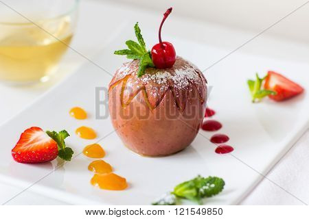 Baked apple with fruit jam on plate