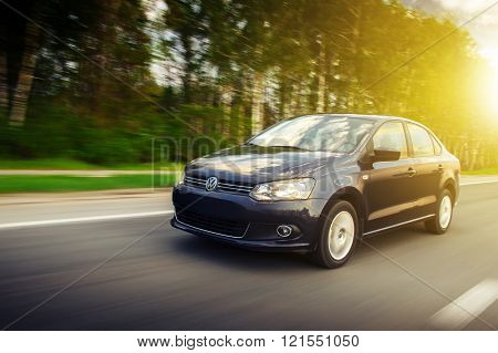 Saratov, Russia - May 6, 2013: Blue car Volkswagen Polo Sedan fast speed drive on the asphalt road at summer sunset near green forest