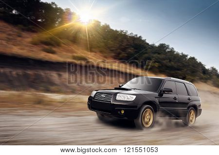 Saratov, Russia - August 14, 2014: Black car Subaru Forester  fast drive on dirt road at summertime sunset