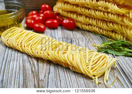 Homemade fettuccini pasta small red tomatoes and olive oil on wooden background diet and food concept. Closeup.
