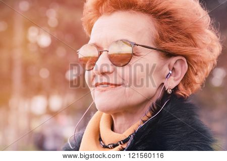 Woman Wearing Headphones And Listening To Music Wearing Winter Clothes