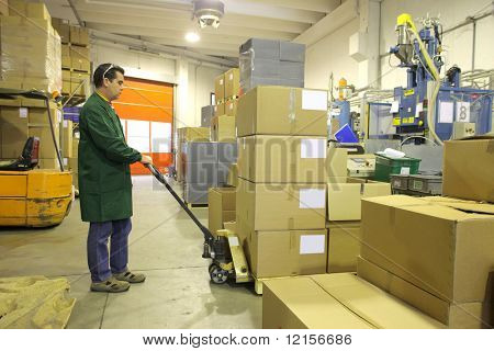 worker with fork lifter in the warehouse