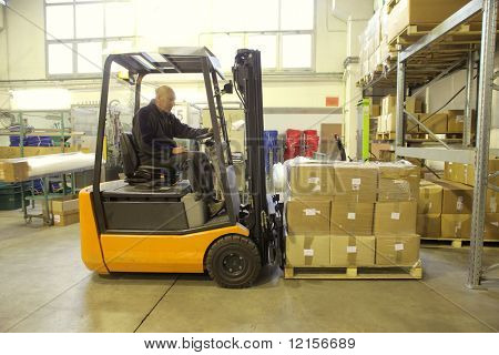worker driving fork lifter in a warehouse