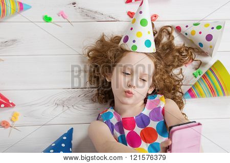 Little girl on wooden floor making selfie photo in birthday party.