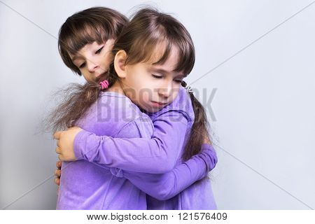Two little girls sister twins in violet dress with long sleeves hug empty place for text